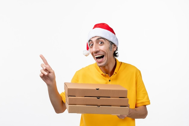 Widok z przodu męski kurier z pudełkami po pizzy na białej ścianie usługa jednolita dostawa