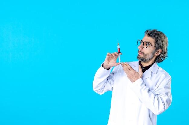 Widok z przodu męski lekarz przygotowujący zastrzyk na niebiesko