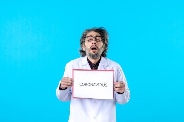 Widok z przodu męski lekarz trzymający koronawirusa piszący na niebiesko
