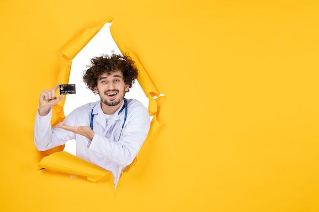 Widok z przodu męski lekarz w garniturze medycznym posiadający kartę bankową na żółtym zgranym kolorze medycyna medycyna wirus choroba szpitalna zdrowie