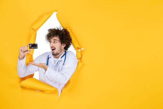 Widok z przodu męski lekarz w garniturze medycznym trzymający kartę bankową na żółtym zgranym kolorze medic wirus choroby szpitalnej zdrowie