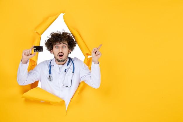 Widok z przodu męski lekarz w garniturze medycznym trzymający kartę bankową na żółtym zgranym kolorze medyka zdrowie medycyna wirus choroby