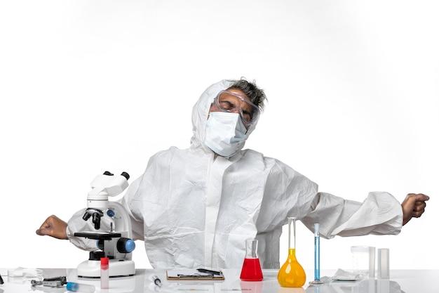 Widok z przodu męski lekarz w kombinezonie ochronnym czuje się zmęczony i ziewa na biało