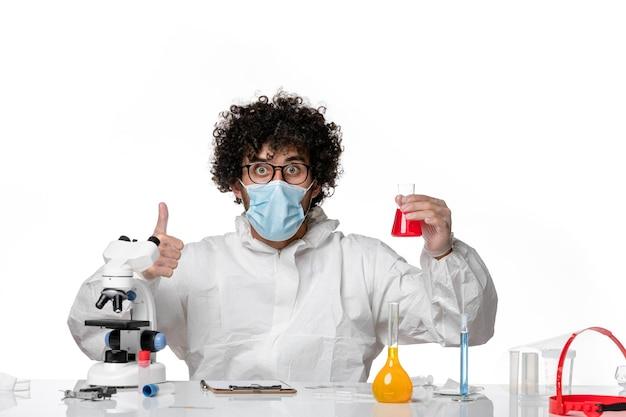 Widok z przodu męski lekarz w kombinezonie ochronnym i masce trzymającej kolbę z czerwonym roztworem na jasnobiałym tle pandemiczny powidok - wirus epidemiczny