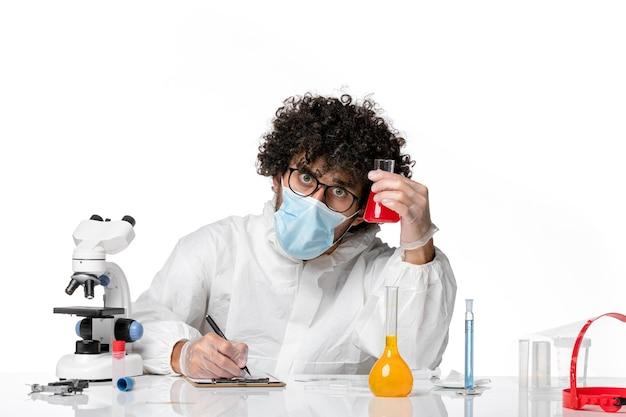 Widok z przodu męski lekarz w kombinezonie ochronnym i masce trzymającej kolbę z czerwonym roztworem, piszący na białym tle pandemiczny covid - wirus epidemiczny