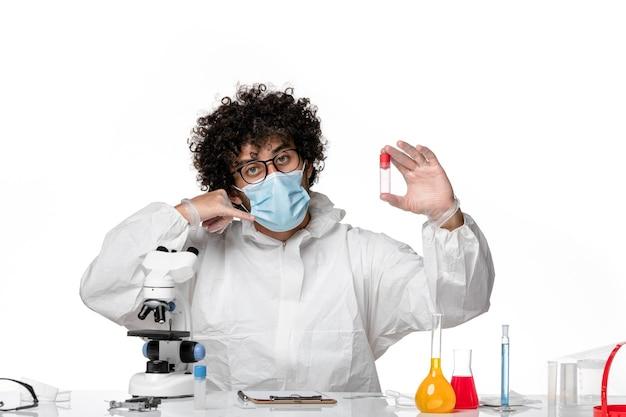 Widok z przodu męski lekarz w kombinezonie ochronnym i masce trzymającej próbkę na białym tle