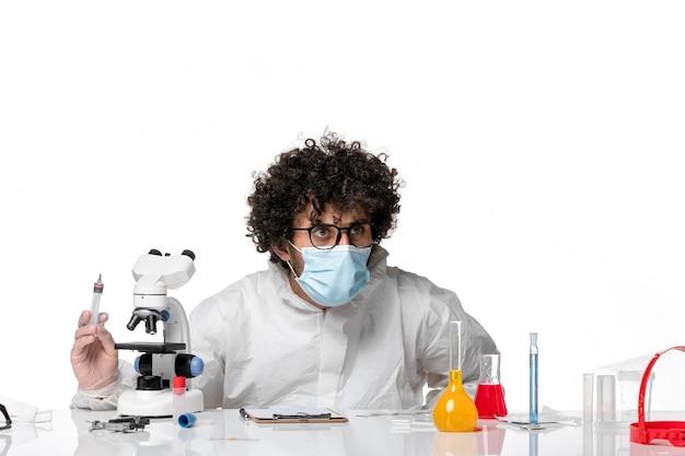 Widok z przodu męski lekarz w kombinezonie ochronnym i masce trzymającej zastrzyk na białym tle