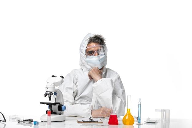 Widok z przodu męski lekarz w kombinezonie ochronnym i sterylną maską myślący na białym tle
