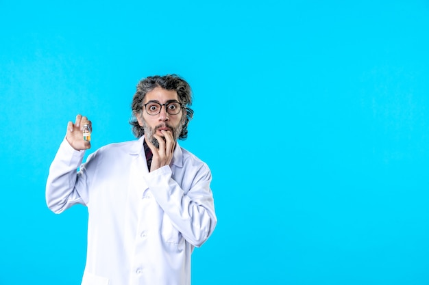 Widok z przodu męski lekarz w mundurze medycznym trzymający małą kolbę na niebiesko