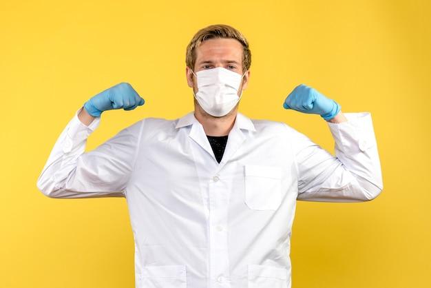 Widok z przodu męski lekarz zginający się w masce na żółtym tle wirus pandemii covid zdrowia