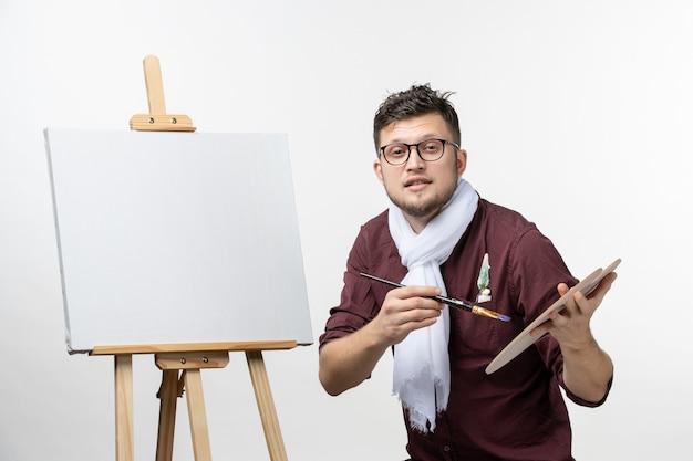 Widok z przodu męski malarz rysujący na sztalugach z pędzlem na białej ścianie