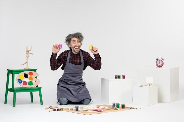 Widok z przodu męski malarz siedzący z farbami i frędzlami do rysowania na białym tle kolor rysunek obraz artysta obrazy sztuka
