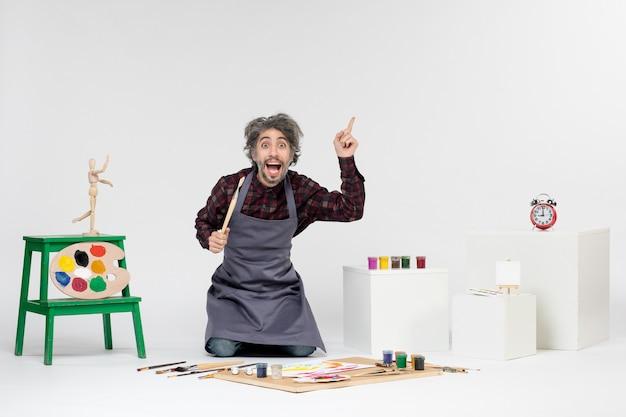 Widok z przodu męski malarz wewnątrz pokoju z farbami i pędzlami do rysowania na białym tle sztuka rysuje mężczyzna artysta maluje kolorowy obraz