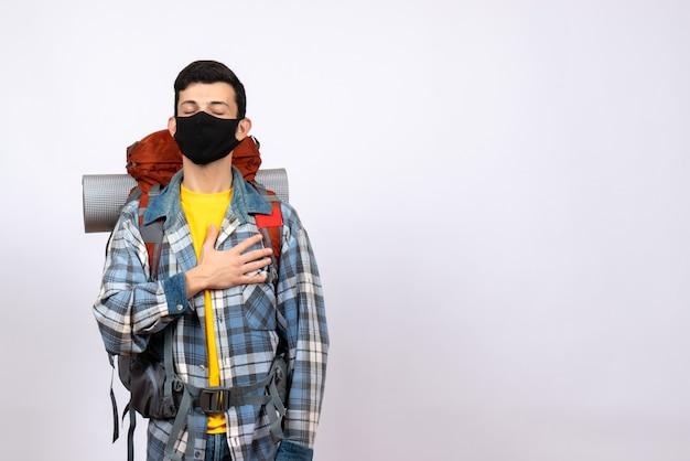 Widok z przodu męski podróżnik z plecakiem i maską kładący dłoń na piersi z zamkniętymi oczami
