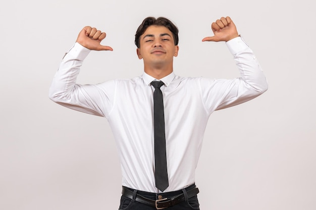 Widok z przodu męski pracownik biurowy czuje się pewnie na białej ścianie praca w biurze ludzkim