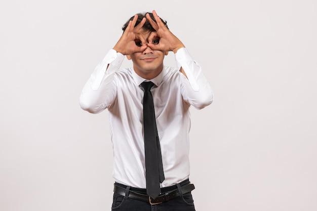 Widok z przodu męski pracownik biurowy patrzący na białą ścianę praca ludzka praca biurowa mężczyzna