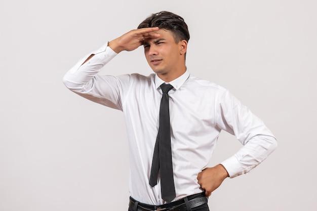 Widok z przodu męski pracownik biurowy patrzący na odległość na białej ścianie praca biznesowa praca męska