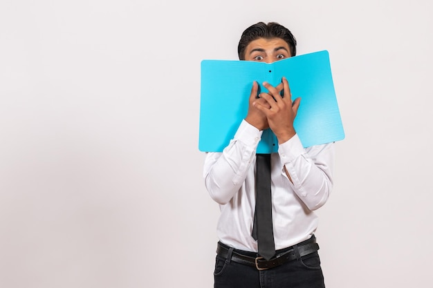 Widok z przodu męski pracownik biurowy sprawdzający dokumenty na białej ścianie praca męska biznesowa