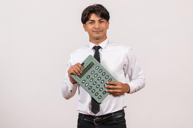 Widok z przodu męski pracownik biurowy trzymający kalkulator na jasnej białej ścianie praca ludzka praca mężczyzna
