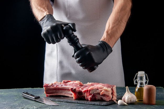Widok z przodu męski rzeźnik nalewający pieprz na plaster mięsa na ciemnej powierzchni