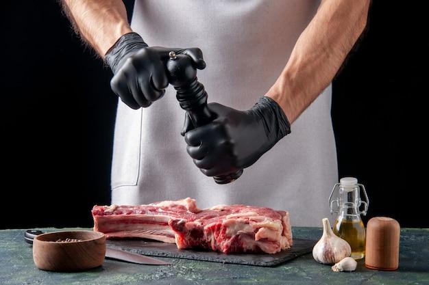 Widok z przodu męski rzeźnik przyprawiający plaster mięsa na ciemnej powierzchni