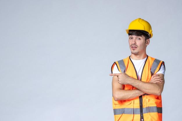 Widok z przodu męskiego budowniczego w mundurze i żółtym kasku na białej ścianie