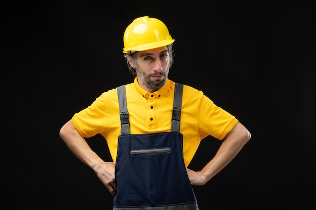 Widok z przodu męskiego budowniczego w mundurze na czarnej ścianie