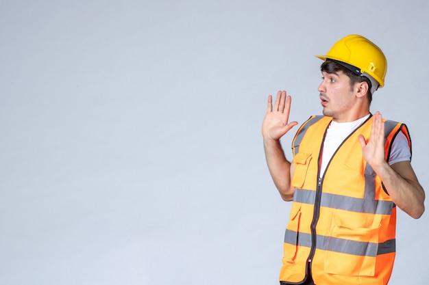 Widok z przodu męskiego budowniczego w mundurze rozmawiającego z kimś na białej ścianie