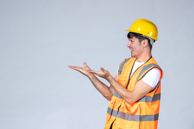 Widok z przodu męskiego budowniczego w mundurze uśmiechającego się do kogoś na białej ścianie
