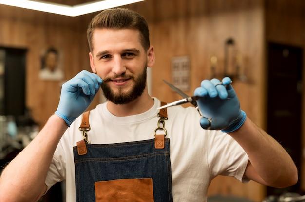 Widok z przodu męskiego fryzjera trzymającego nożyczki w zakładzie fryzjerskim