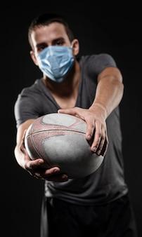 Widok z przodu męskiego gracza rugby z maską medyczną trzymając piłkę