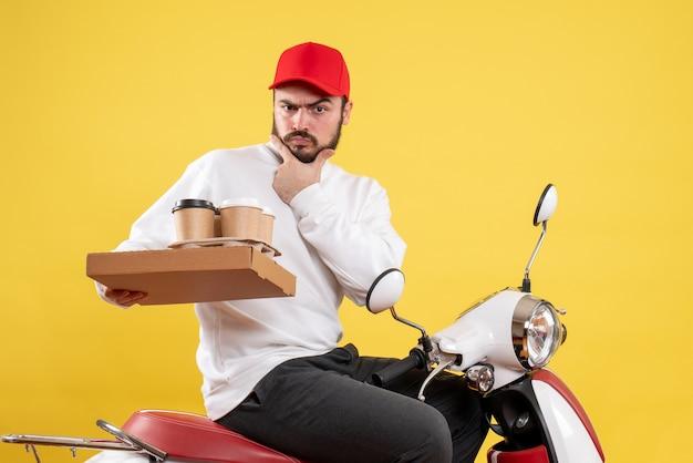 Widok z przodu męskiego kuriera trzymającego dostawę kawy i żywności na żółtej ścianie