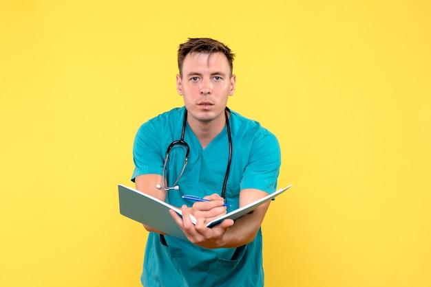 Widok z przodu męskiego lekarza posiadającego analizy na żółtej ścianie