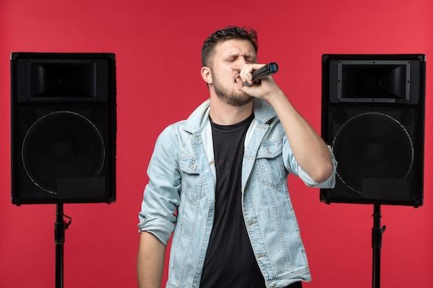 Widok z przodu męskiego piosenkarza występującego na scenie z systemem stereo na czerwonej ścianie