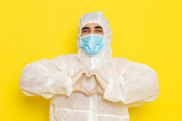Widok z przodu męskiego pracownika naukowego w specjalnym białym kombinezonie ochronnym z maską na jasnożółtym biurku pracownik naukowy chemia naukowa kolor niebezpieczeństwa