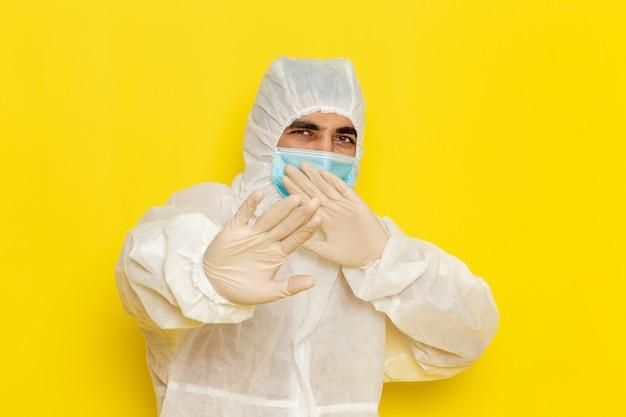 Widok z przodu męskiego pracownika naukowego w specjalnym kostiumie ochronnym iz maską pozującego na jasnożółtej ścianie