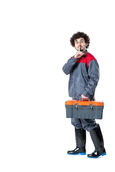 Widok z przodu męskiego pracownika w jednolitej walizce z narzędziami na białej ścianie