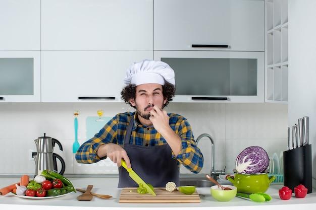 Widok z przodu męskiego szefa kuchni z kwaśną twarzą ze świeżymi warzywami i gotowaniem za pomocą narzędzi kuchennych i degustacją zielonej papryki w białej kuchni