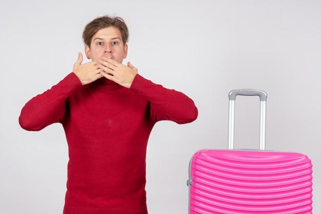 Widok z przodu męskiego turysty z różową torbą na białej ścianie