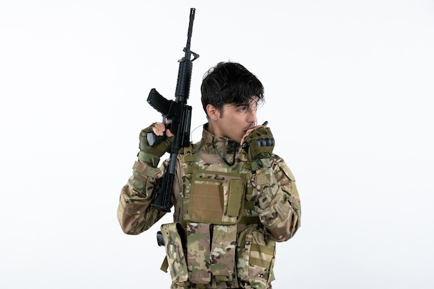 Widok z przodu męskiego żołnierza w kamuflażu z białą ścianą karabinu maszynowego