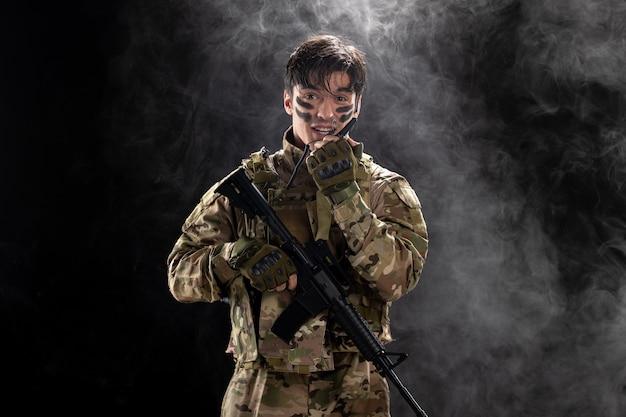 Widok z przodu męskiego żołnierza z karabinem maszynowym za pomocą czarnej ściany walkie-talkie