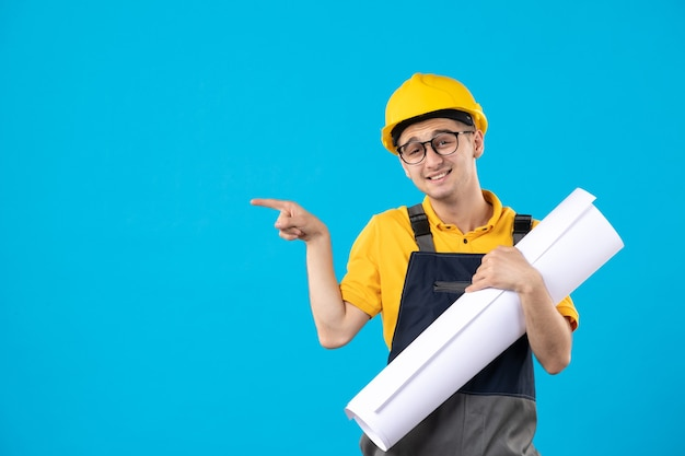 Widok z przodu mężczyzna budowniczy w mundurze z planem papieru na niebiesko