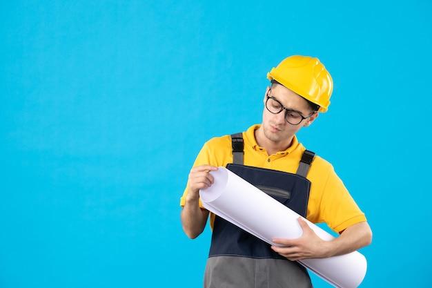 Widok z przodu mężczyzna budowniczy w żółtym mundurze z planem papieru na niebiesko
