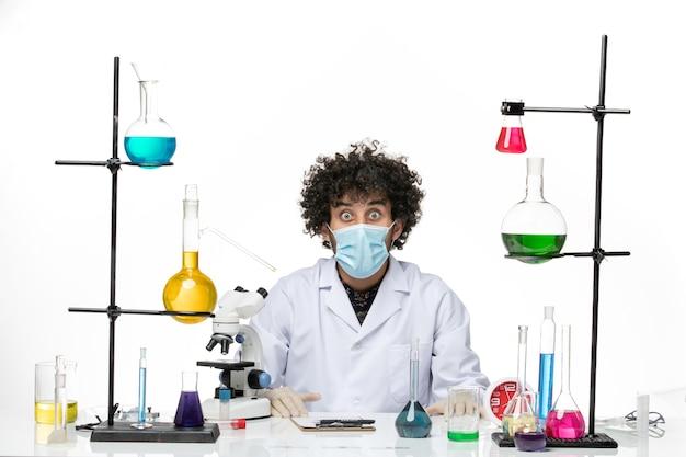 Widok z przodu mężczyzna chemik w białym garniturze medycznym iz maską, patrząc zszokowany wyraz twarzy na białej przestrzeni