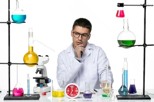 Widok z przodu mężczyzna chemik w białym garniturze medycznym przygotowuje się do pracy i myśli na białym tle wirus choroby laboratorium naukowe covid
