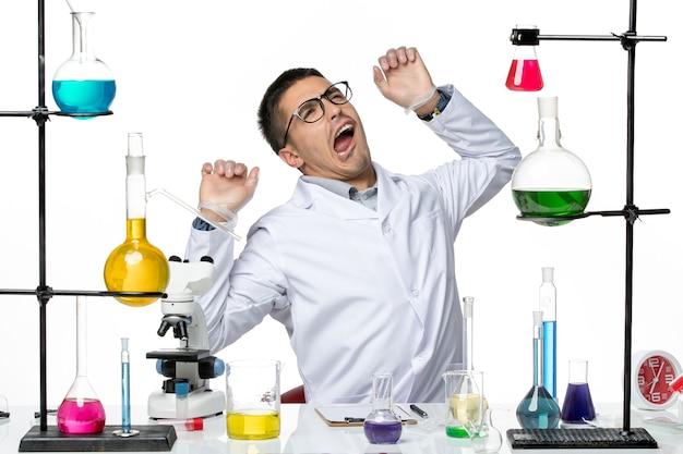 Widok z przodu mężczyzna chemik w białym garniturze medycznym przygotowuje się do pracy na białym tle wirus choroby laboratorium naukowe covid