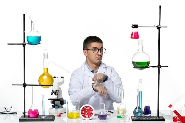 Widok z przodu mężczyzna chemik w białym garniturze medycznym siedzący z różnymi roztworami na białej podłodze laboratorium choroby wirusowe laboratorium naukowe