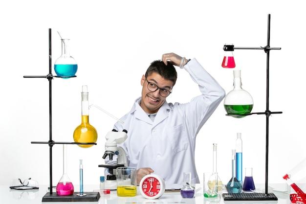 Widok z przodu mężczyzna chemik w białym kombinezonie medycznym siedzący i przygotowujący się do pracy na jasnym białym tle wirus naukowy covid - laboratorium pandemiczne