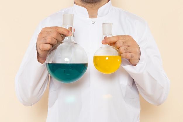 Widok z przodu mężczyzna chemik w białym specjalnym garniturze trzymający kolby roztworów na biurku z kremem laboratorium naukowe eksperyment chemia naukowa