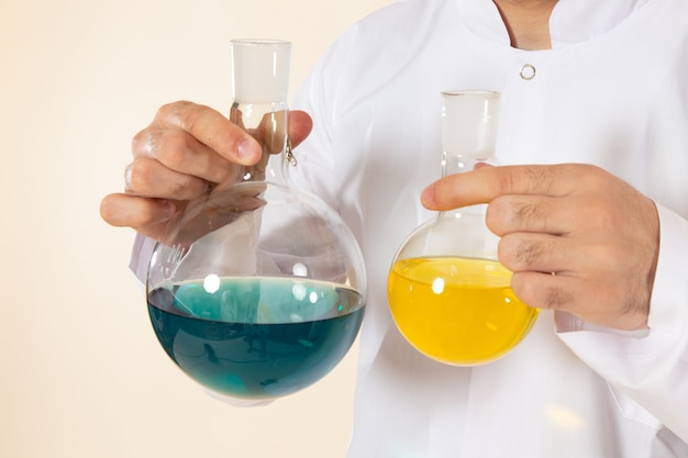 Widok z przodu mężczyzna chemik w białym specjalnym garniturze trzymający kolby z roztworami na kremowej ścianie laboratorium naukowe eksperyment chemia naukowa